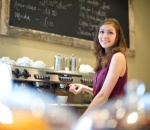 Young woman making coffee in a cafe