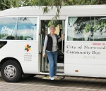 Image of a woman stepping out of the community bus